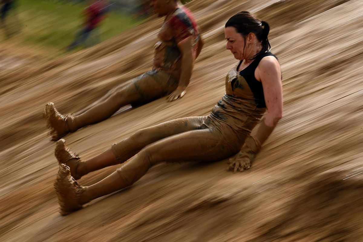 """Participants compete in the """"Mud day challenge"""", a 13-kilometre obstacles course, on May 7, 2016 in Beynes near Paris."""