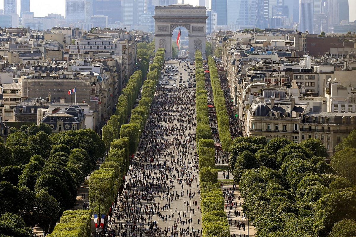 People walk on the car-free Champs-Elysees avenue in Paris, France, on May 8, 2016.