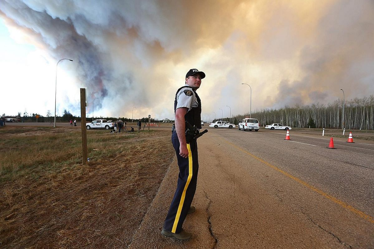Smoke and flames from the wildfires erupting behind a car (top) on a highway near Fort McMurray last week. Huge plumes of smoke (above) from an out-of-control wildfire, one of many which have ravaged Canada's oil hub in northern Alberta. Estimates of