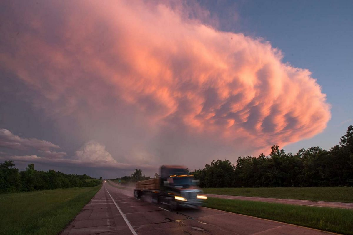A truck drives as a supercell storm system baring multiple tornado warnings expands across the sky near Hugo, Oklahoma, on May 9, 2016.