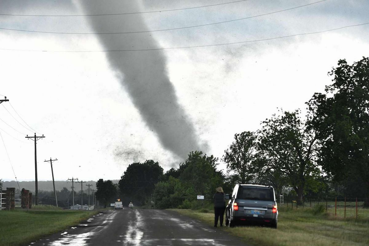 A woman looks on while a tornado rips through a residential area after touching down south of Wynnewood, Oklahoma, on May 9, 2016.