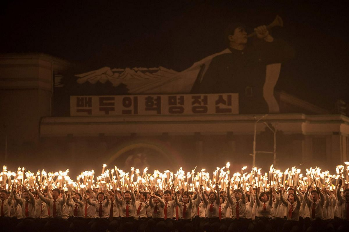 Performers take part in a torchlight parade on Kim Il-Sung square during festivities marking the end of the 7th Workers Party Congress in Kim Il-Sung square in Pyongyang on May 10, 2016.