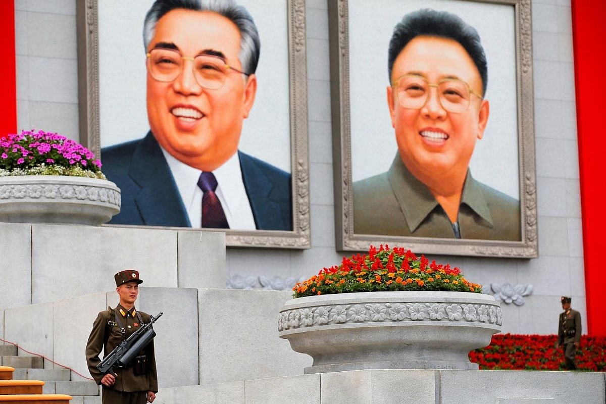 Soldiers stand under pictures of former North Korean leaders Kim Il Sung and Kim Jong Il at the capital's main ceremonial square in Pyongyang, North Korea, on May 10, 2016.