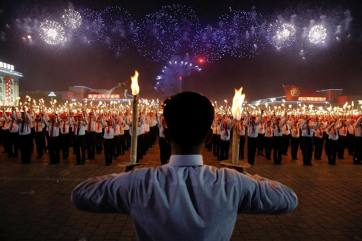 Fireworks explode over participants carrying torches during a torchlight procession in the capital's main ceremonial square in Pyongyang, North Korea, on May 10, 2016.