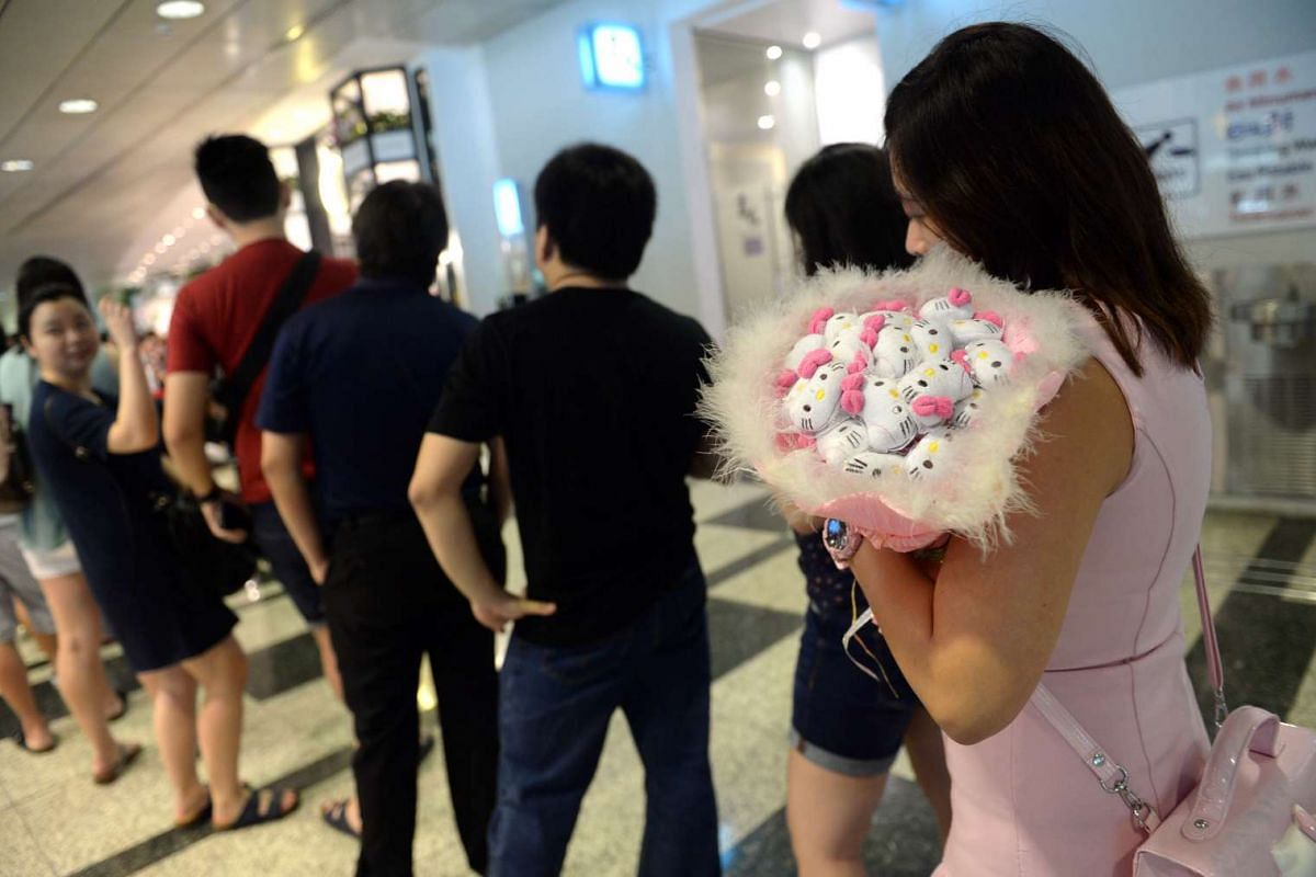 A patron holds a bouquet of miniature Hello Kitty toys while queuing outside the Hello Kitty themed cafe in Changi Airport Terminal 3's Arrival Hall, on May 12, 2016.