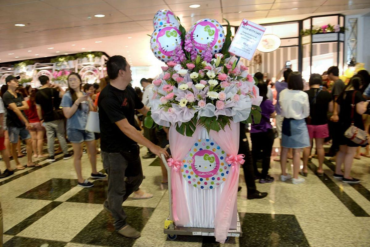 A man moves a congratulatory flower stand outside the Hello Kitty cafe during its opening at Changi Airport Terminal 3, on May 12, 2016.