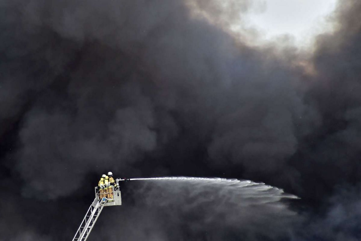 Firemen on a ladder are engulfed in smoke as they douse a fire in a storage facility with water at the Dong Xuan shopping centre in Berlin's Lichtenberg district, on May 11, 2016.