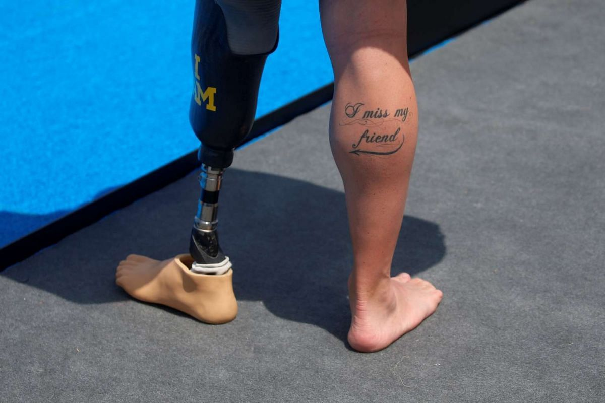 """Mike Goody of Britain shows a tattoo which reads """"I miss my friend"""", referring to his lost leg, during a medal ceremony at the Invictus Games in Orlando, Florida, on May 11, 2016."""