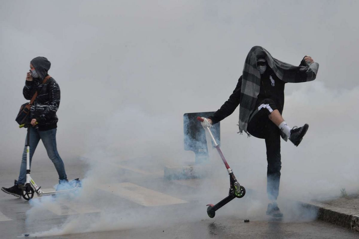 Protesters throw tear gas grenade back to riot police during a demonstration against the government's proposed labour reform in Nantes, France, on May 13, 2016.