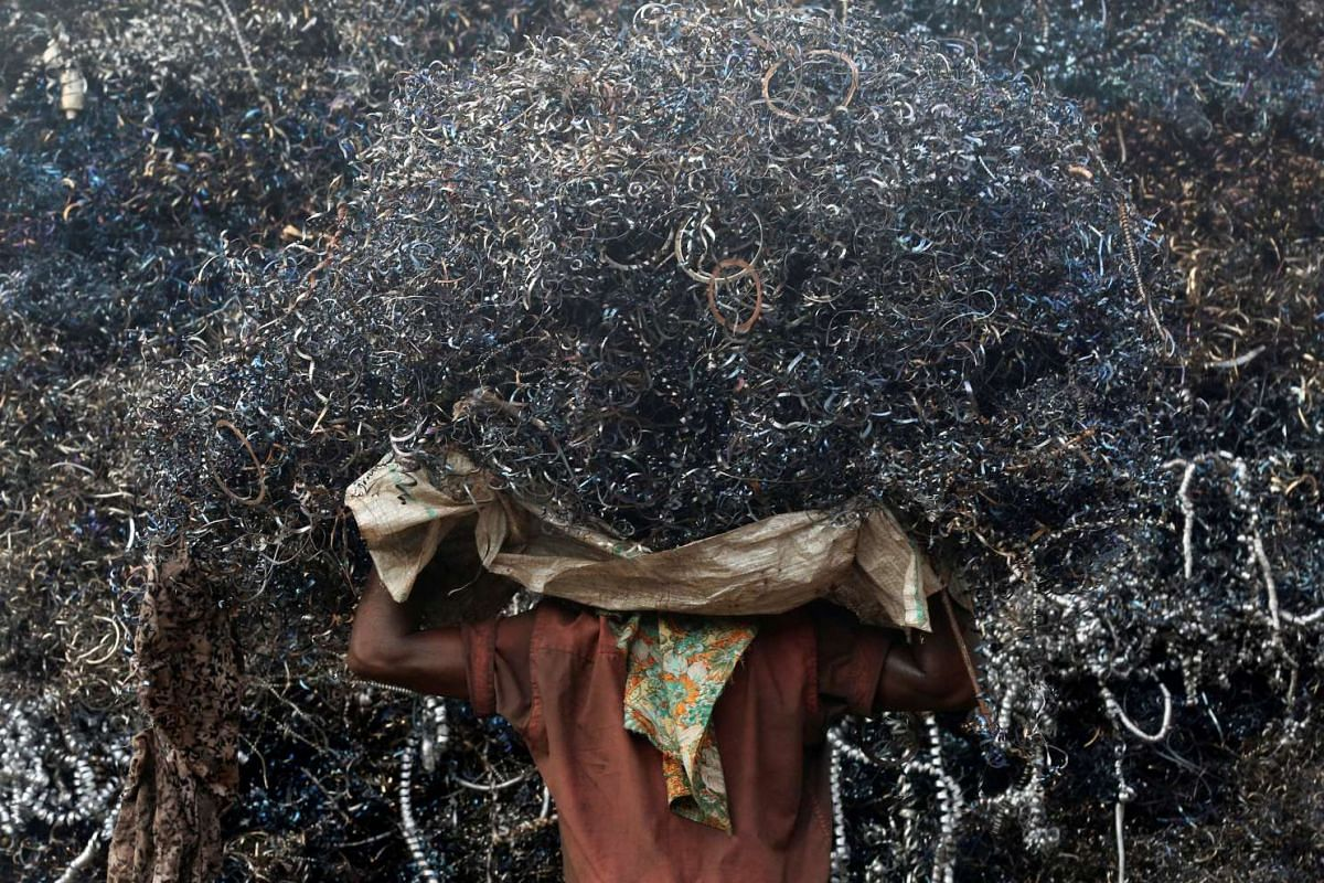 A labourer loads metal scrap onto a truck in an industrial area in Mumbai, India, on May 12, 2016.