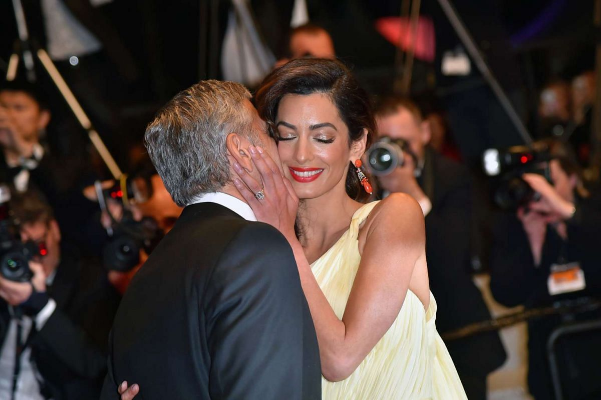 American actor George Clooney (left) kisses his wife, British-Lebanese lawyer Amal Clooney, after the screening of the film Money Monster at the 69th Cannes Film Festival on May 12.