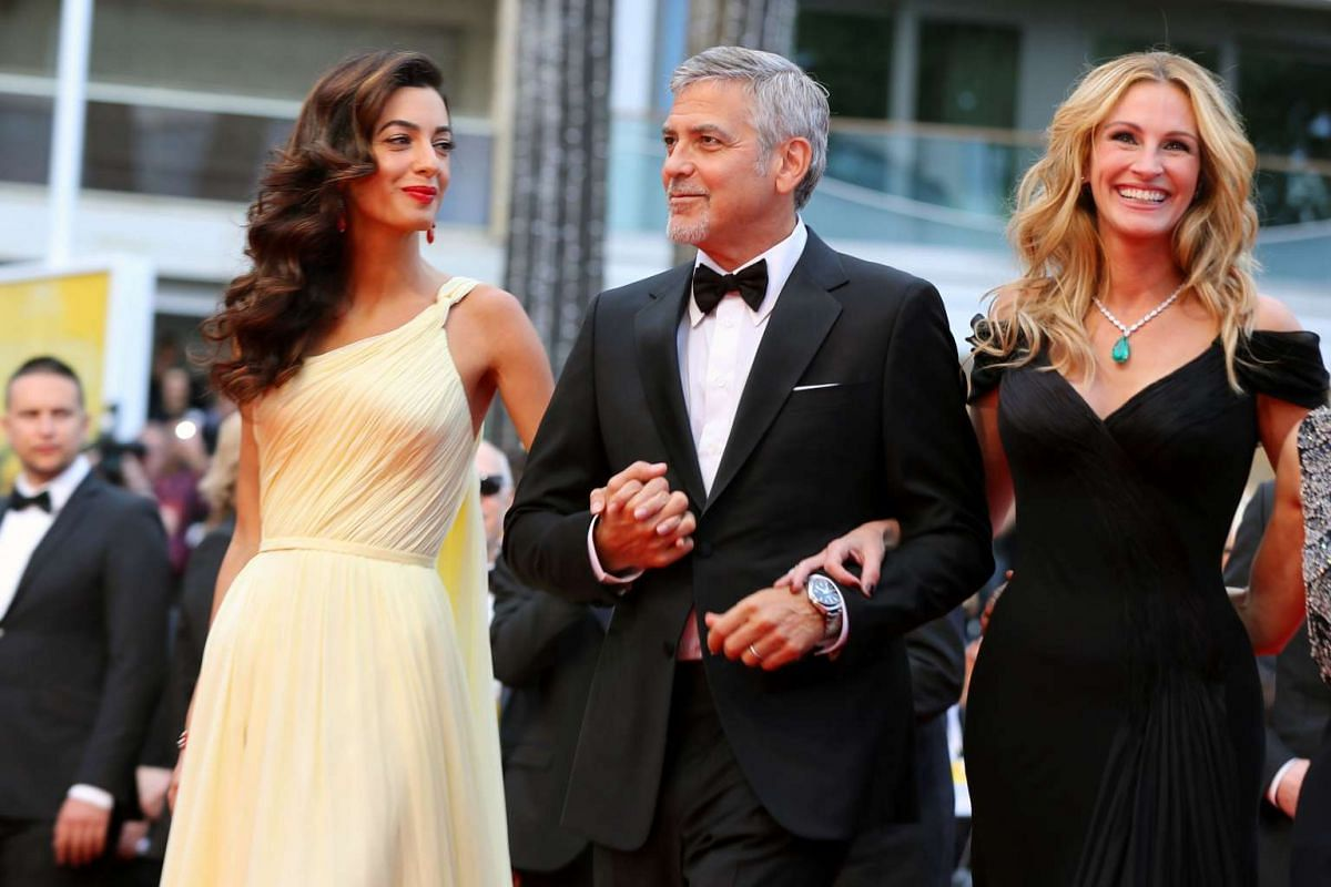 George Clooney (centre), his wife Amal (left), and actress Julia Roberts arriving for the screening of Money Monster.