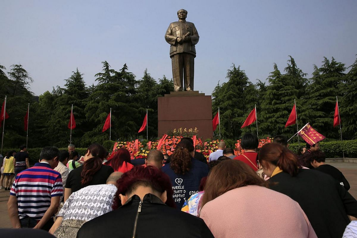 Visitors bowing in front of Mao Zedong's giant statue on Mao Zedong Bronze Statue Square in Shaoshan, Hunan Province in central China, on April 28, 2016.