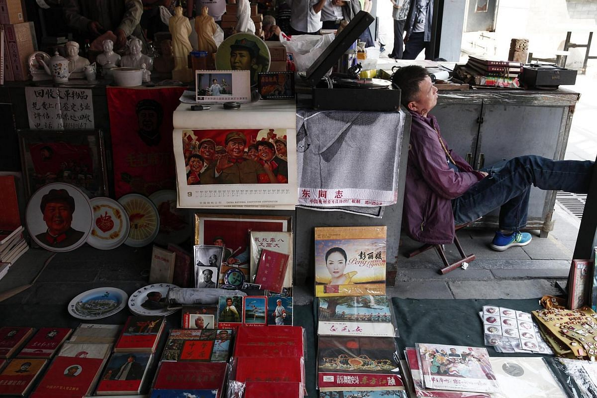 A vendor resting beside his stall that displays various items depicting the late Chinese leader Mao Zedong at the Panjiayuan flea market in Beijing, China, on May 8, 2016.
