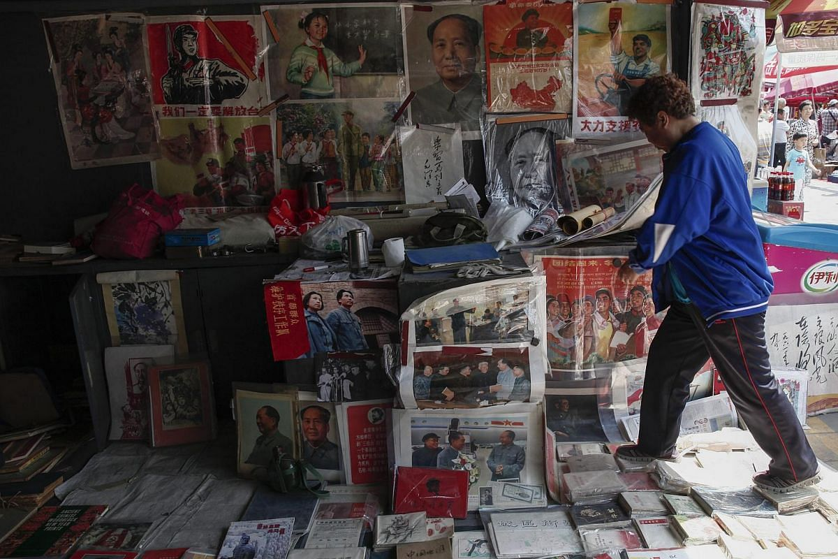 A vendor tending to her stall that displays various items depicting the late Chinese leader Mao Zedong and other items with a Cultural Revolution theme at the Panjiayuan flea market in Beijing, China, on May 8, 2016.