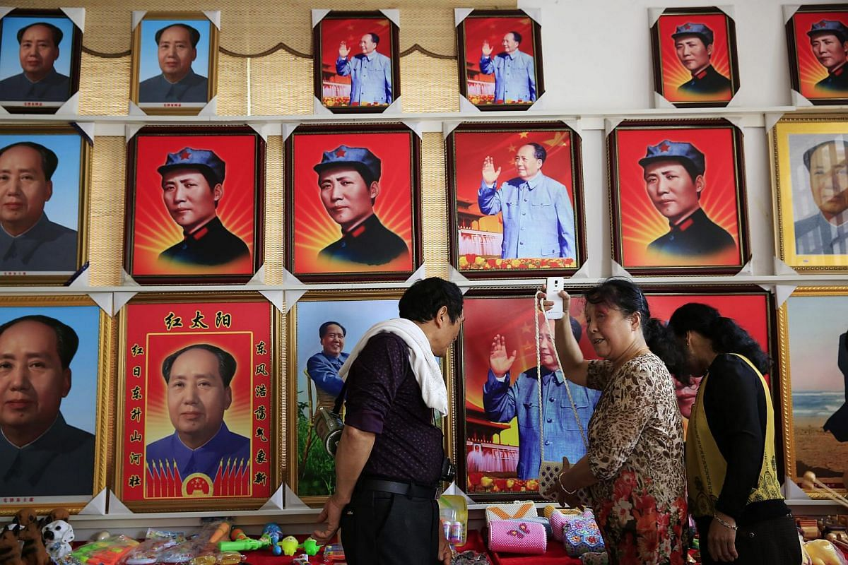 Visitors looking at souvenirs in front of portraits of Mao Zedong at a wholesale souvenir store in Shaoshan, Hunan Province in central China, on April 28, 2016.