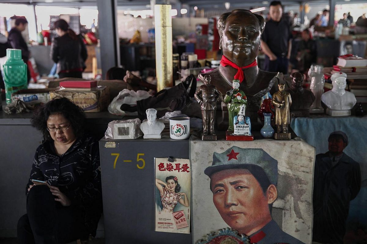 A vendor sitting beside a stall that displays various items depicting the late Chinese leader Mao Zedong at the Panjiayuan flea market in Beijing, China, on May 8, 2016.