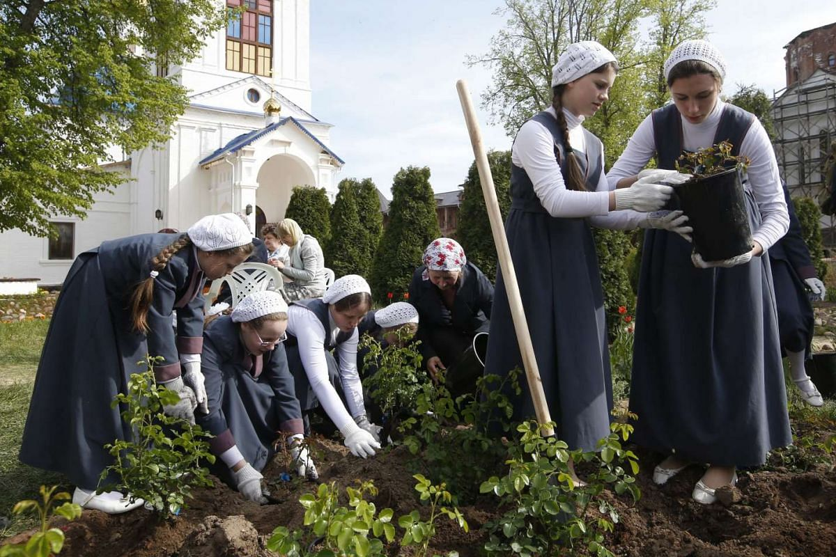 Pupils of a monastery plant roses during the monastery festival of hospitality in St. Nicholas Solba monastery in Yaroslavl region, Russia, on May 15, 2016.