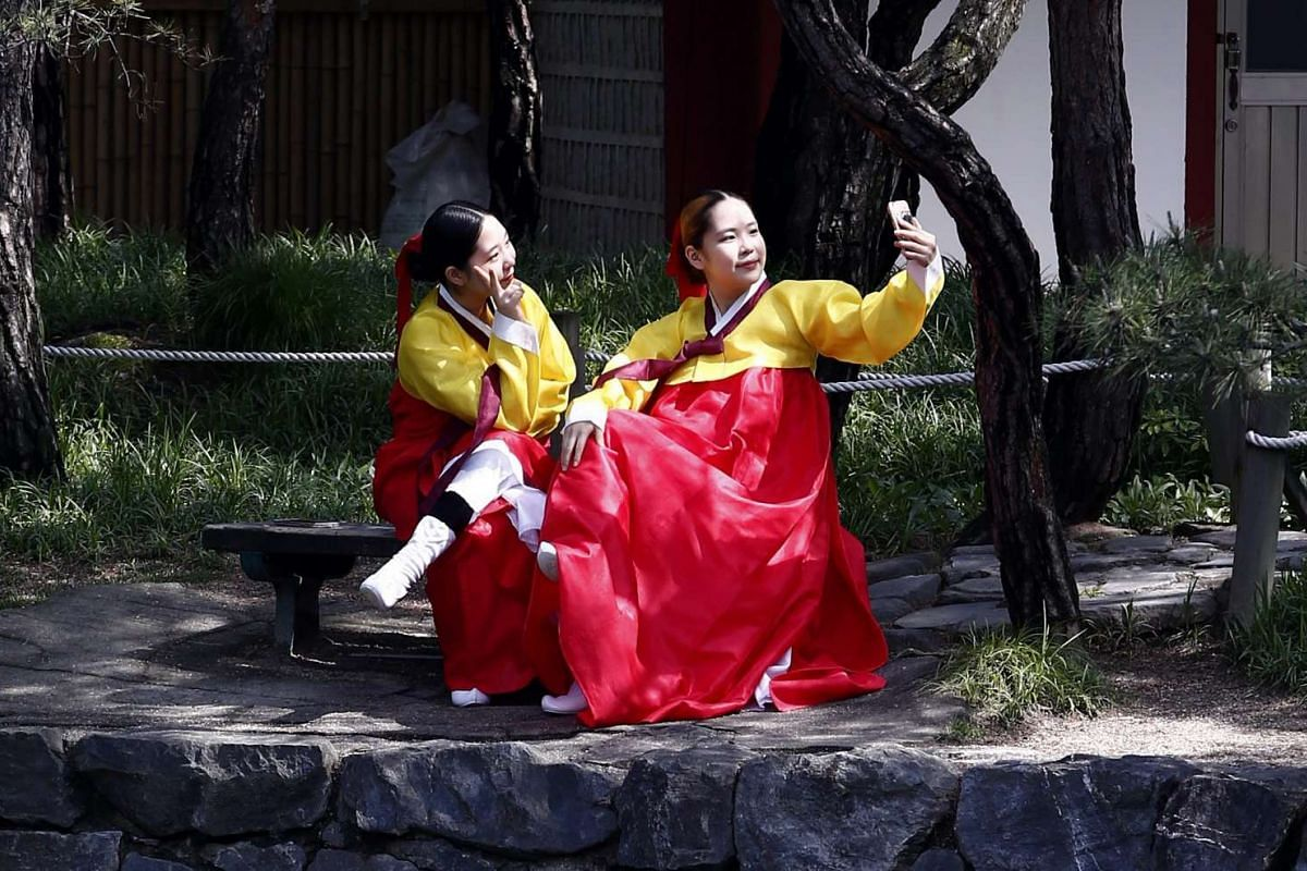 20-year-old South Korean women in traditional costumes pose for a selfie, prior to the 44th Coming-of-Age Day ceremony at Namsangol Hanok Village in Seoul, on May 16, 2016.
