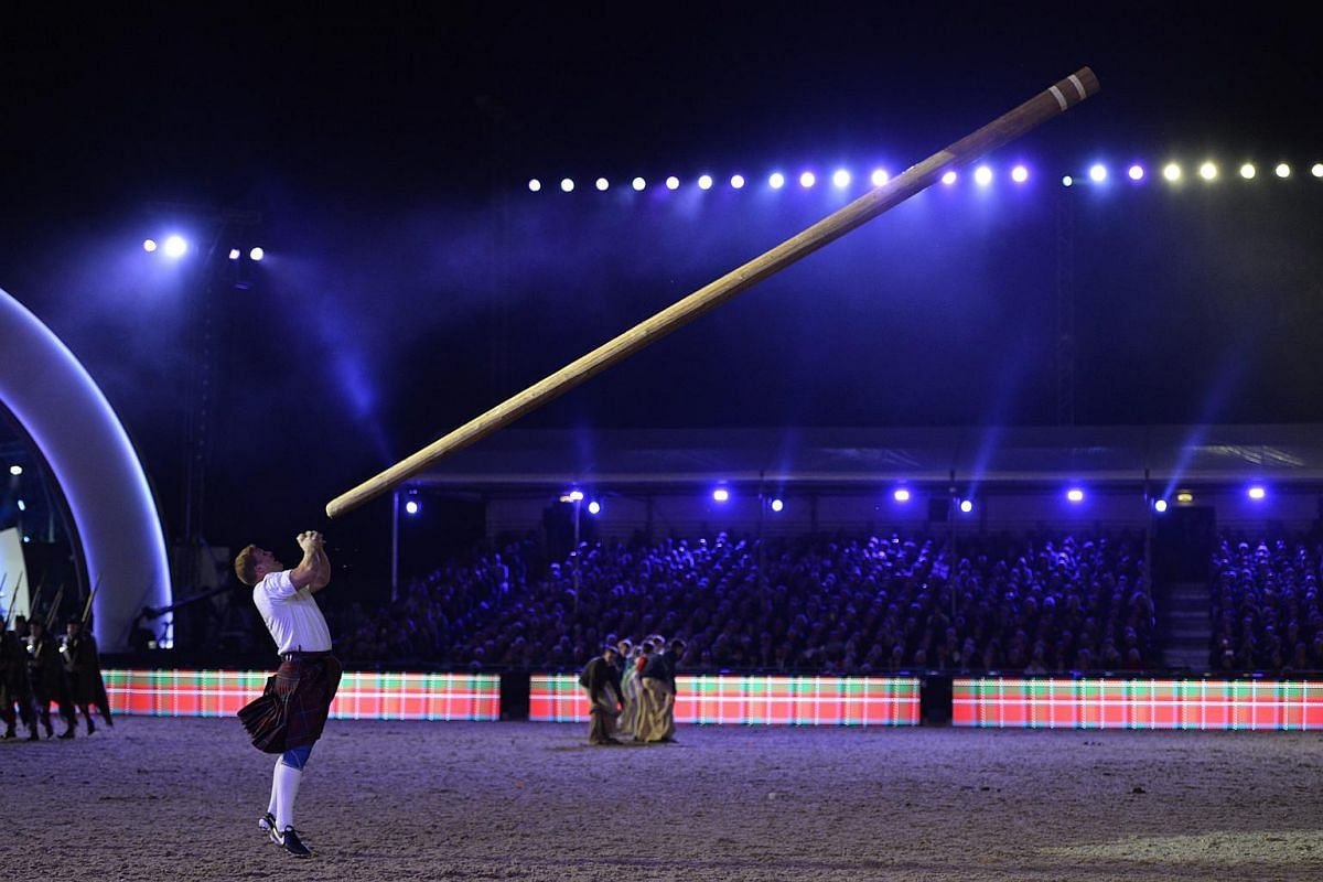 A Scotsman tosses the caber during Queen Elizabeth II's 90th birthday celebrations at the Royal Windsor Horse Show in the grounds of Windsor Castle on May 15, 2016.