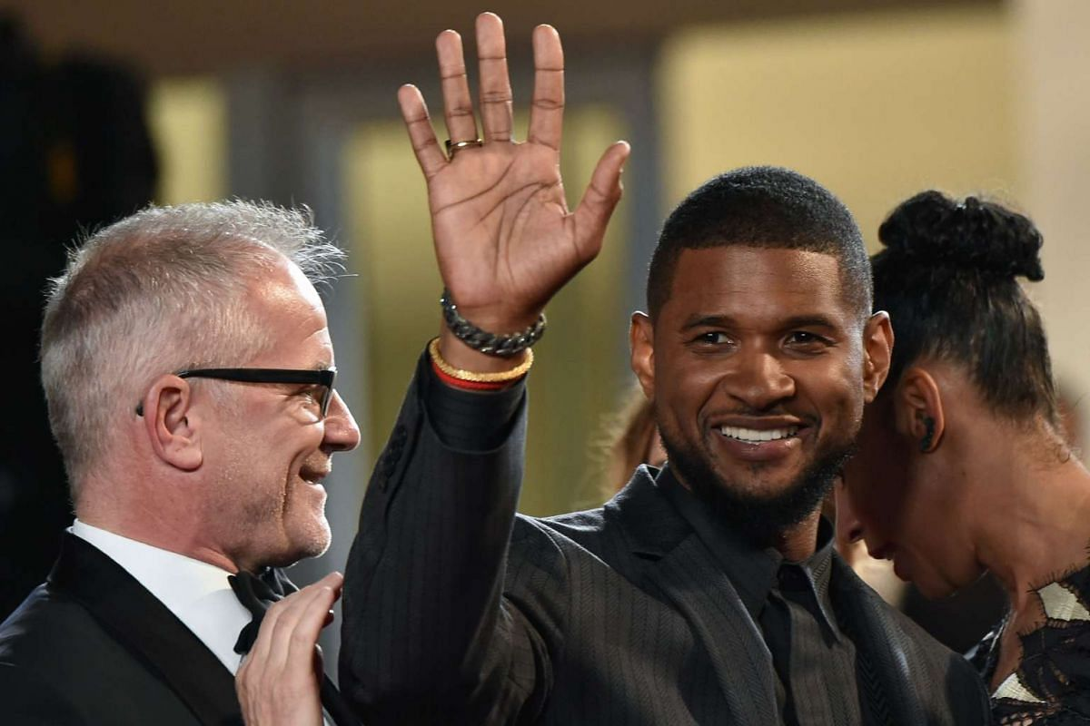 US singer and actor Usher Raymond IV (centre) gestures next to General Delegate of the Cannes Film festival Thierry Fremaux as he arrives for the screening of Hands Of Stone.