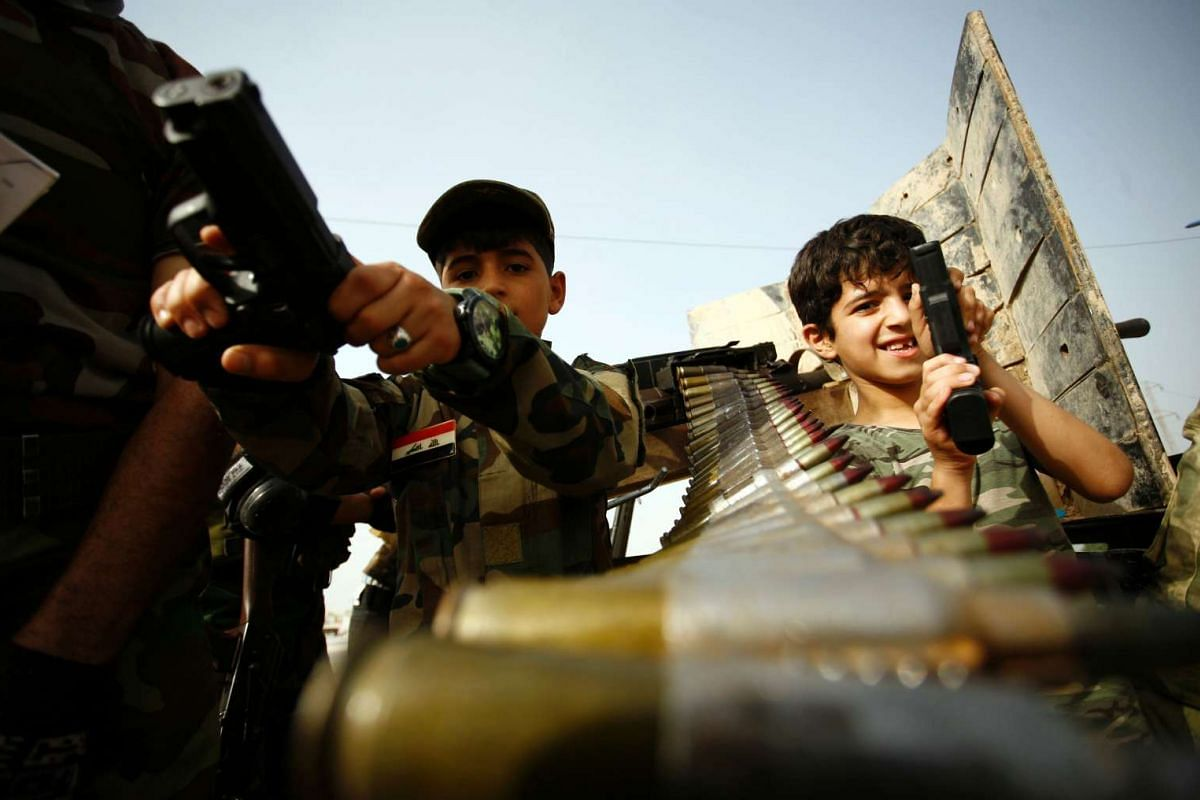 Young supporters of the Saraya al-Salam (Peace Brigades) hold weapons in Iraq's holy city of Najaf as the paramilitary group prepare to reinforce government forces in the fight against the Islamic State group for control of Fallujah, east of the capi