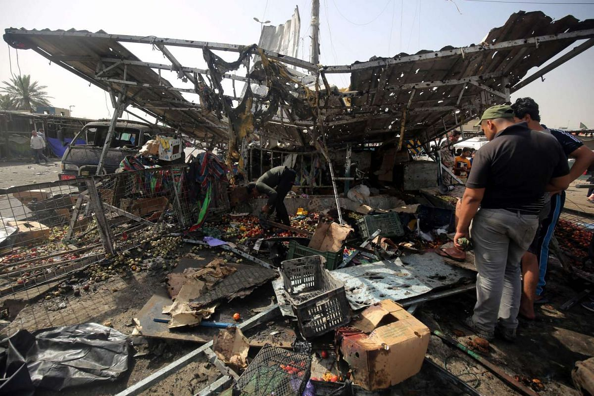 Iraqis check the damage after a suicide bomber detonated an explosives-rigged vehicle in northern Baghdad's Sadr City on May 17, 2016. PHOTO: AFP