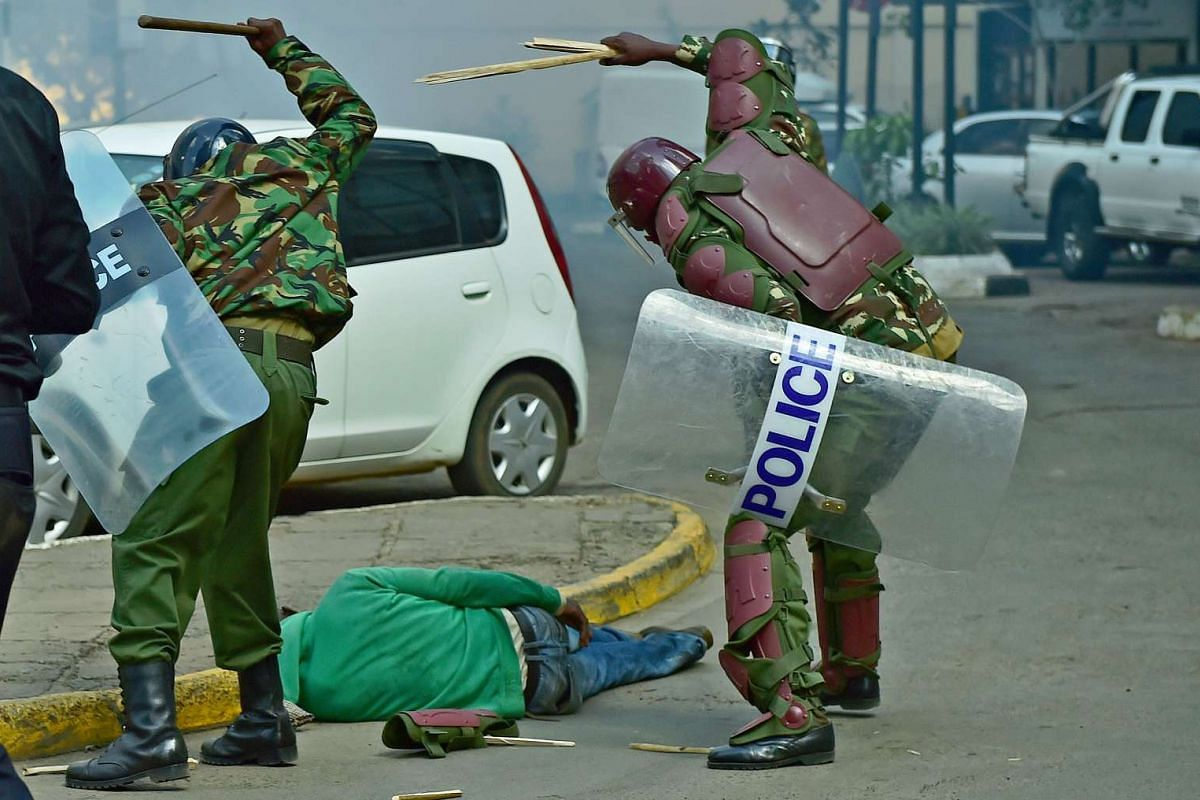 A picture taken on May 16, 2016 in Nairobi shows Kenyan riot police beating an unresponsive fallen protester with wooden sticks and repeatedly kick him several times. The incident has caused Kenya's police chief to order an internal investigation int