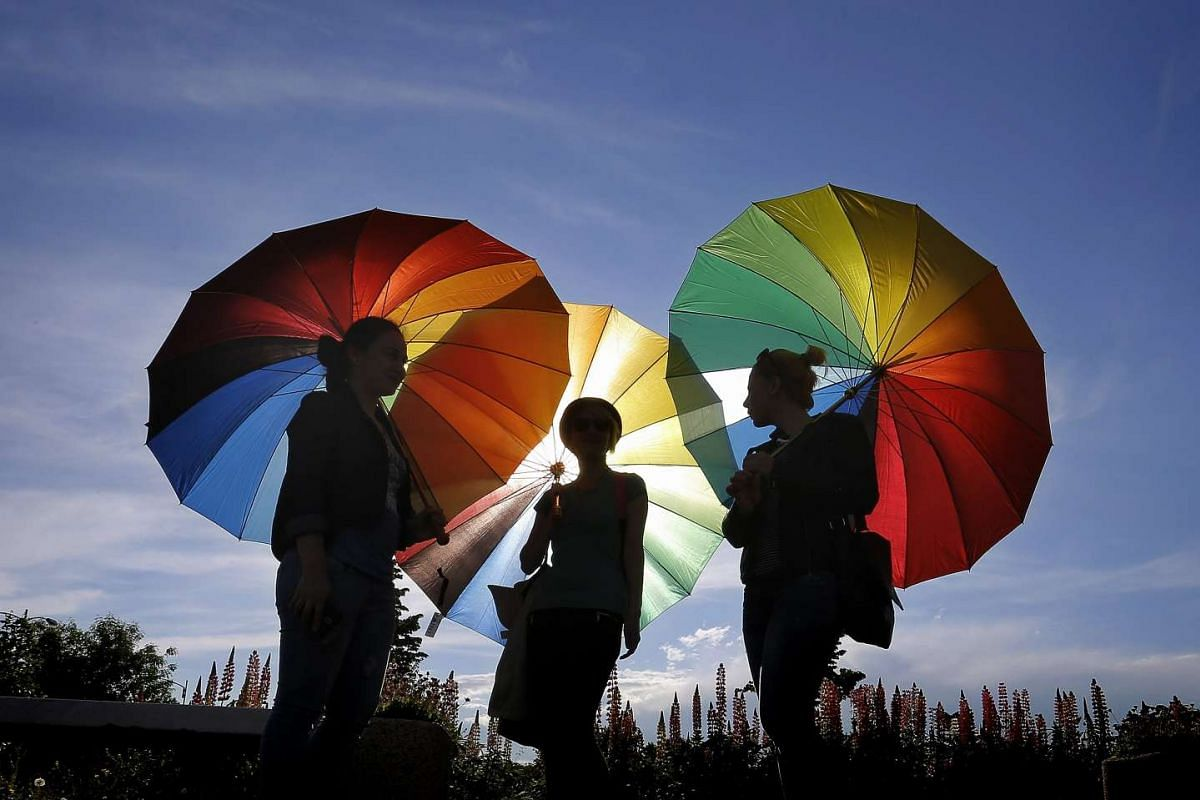 Romanian revellers hold rainbow-colored umbrellas during a flashmob for the gay rights held in front of the Parliament Palace in Bucharest, Romania, May 17, 2016, as part of worldwide commemorations of the International Day Against Homophobia and Tra