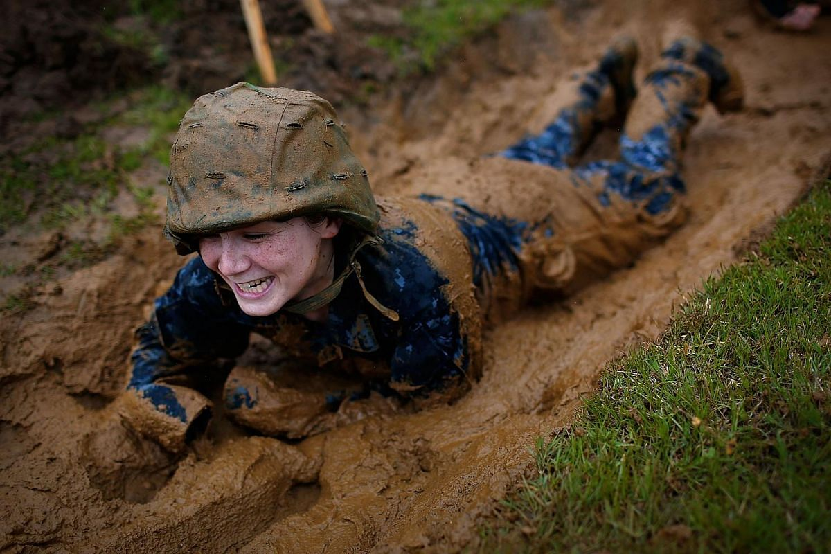 A Naval Academy plebe working her way through a mud filled trench during the annual Sea Trials on May 17, 2016.