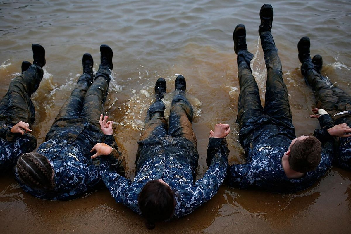 """Naval Academy plebes linking arms while doing sit ups and taking part in the """"Wet and Sandy"""" portion of the annual Sea Trials on May 17, 2016."""