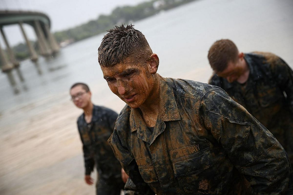"""Naval Academy plebes, covered in sand and mud, finish taking part in the """"Wet and Sandy"""" portion of the annual Sea Trials on May 17, 2016."""