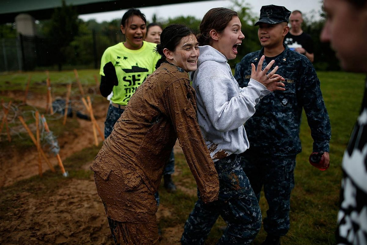 A Naval Academy plebe surprising a friend with a muddy hug after working her way through a mud filled trench during the annual Sea Trials on May 17, 2016.