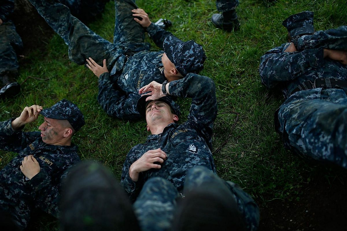 Naval Academy plebes catching their breath after seven hours of intense physical activity at the midpoint of the annual Sea Trials on May 17, 2016.