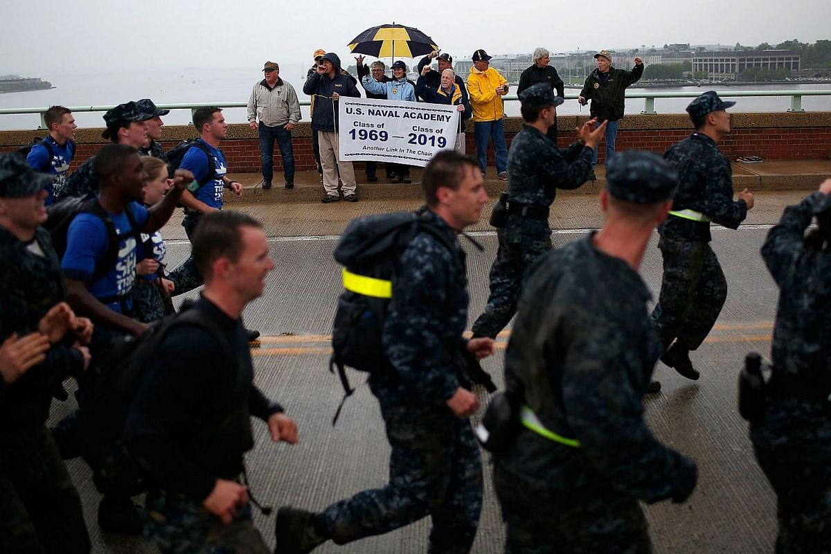 Members of the plebe class of 1969 cheering as Naval Academy plebes from the class of 2019 run across the Naval Academy Bridge at the annual Sea Trials on May 17, 2016.
