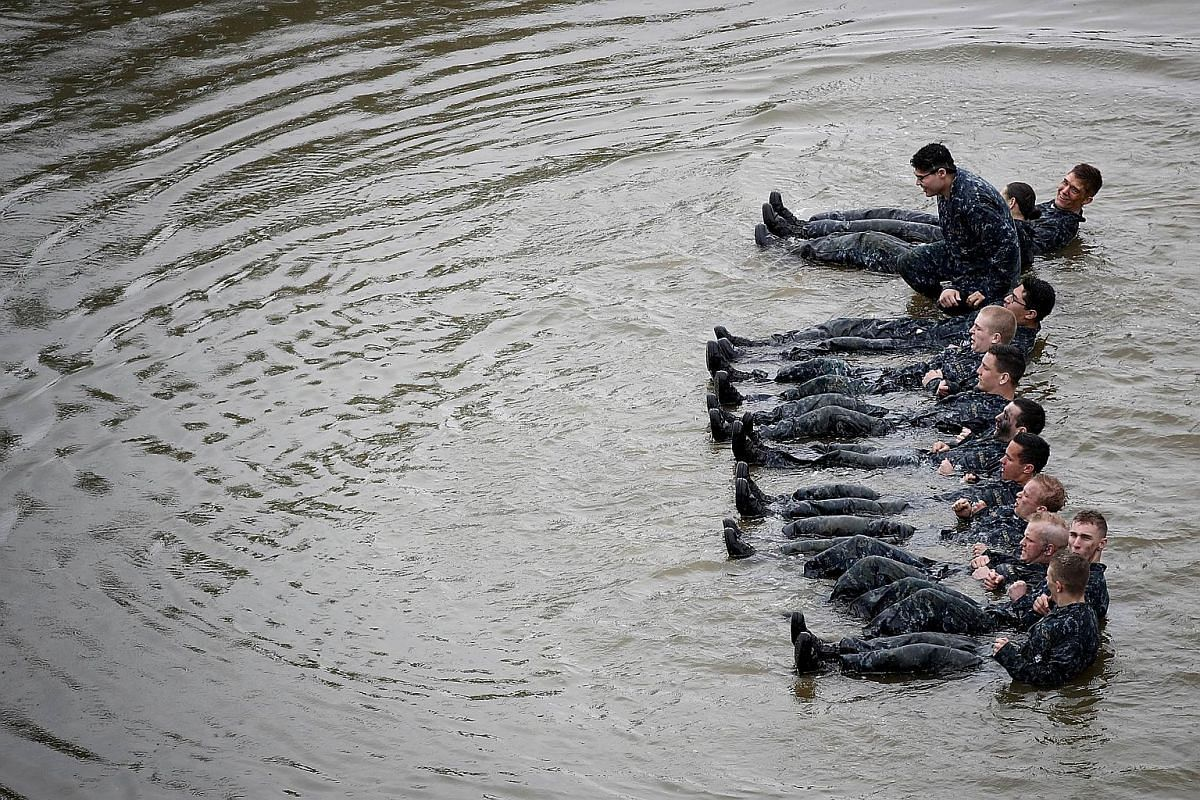 """Naval Academy plebes doing sit ups in the Severn River while taking part in the """"Wet and Sandy"""" portion of the annual Sea Trials on May 17, 2016."""