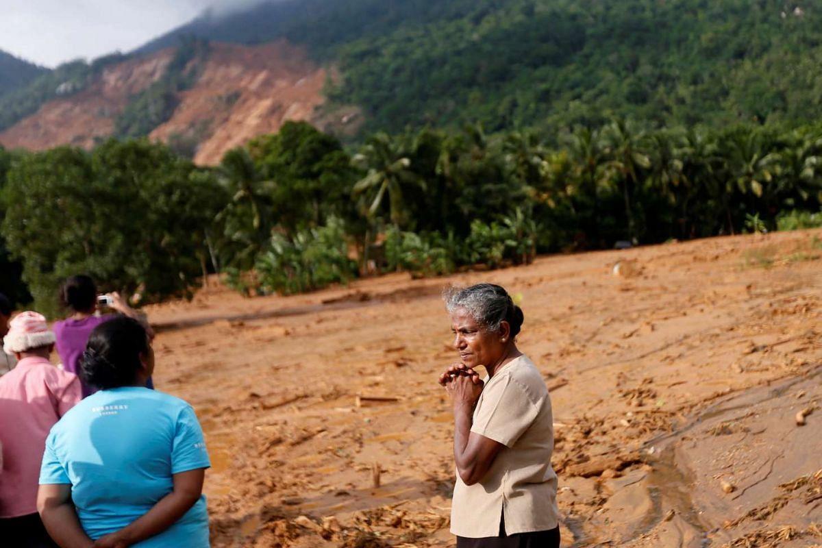 A woman reacts as she inspects the landslide site at Elangipitiya village in Aranayaka , Sri Lanka May 19, 2016. PHOTO: REUTERS