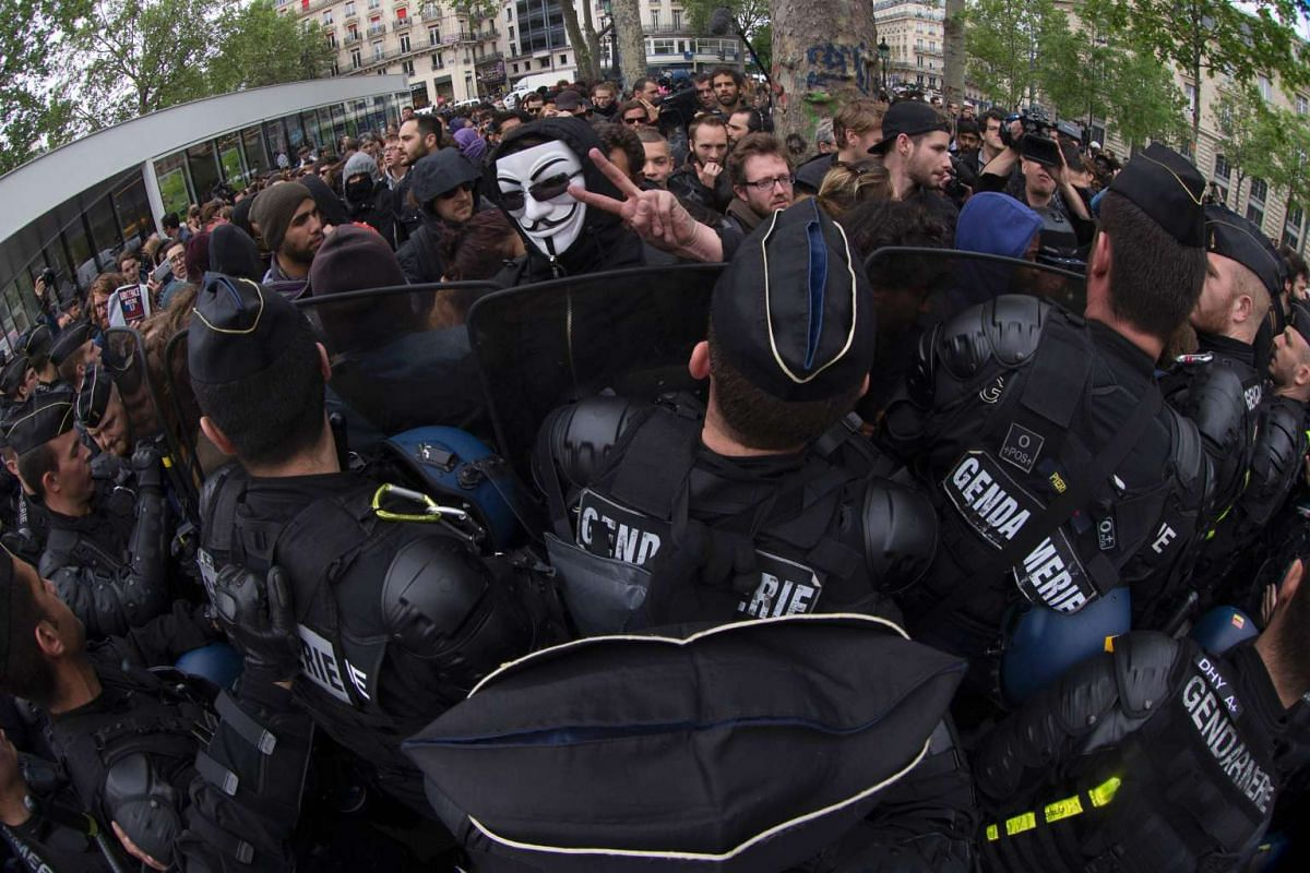 """A demonstrator wearing a Guy Fawkes mask gestures as demonstrations clash with police during a counter-demonstration to a rally of police officers against """"anti-police hatred"""" on May 18, 2016 in Paris. PHOTO: AFP"""