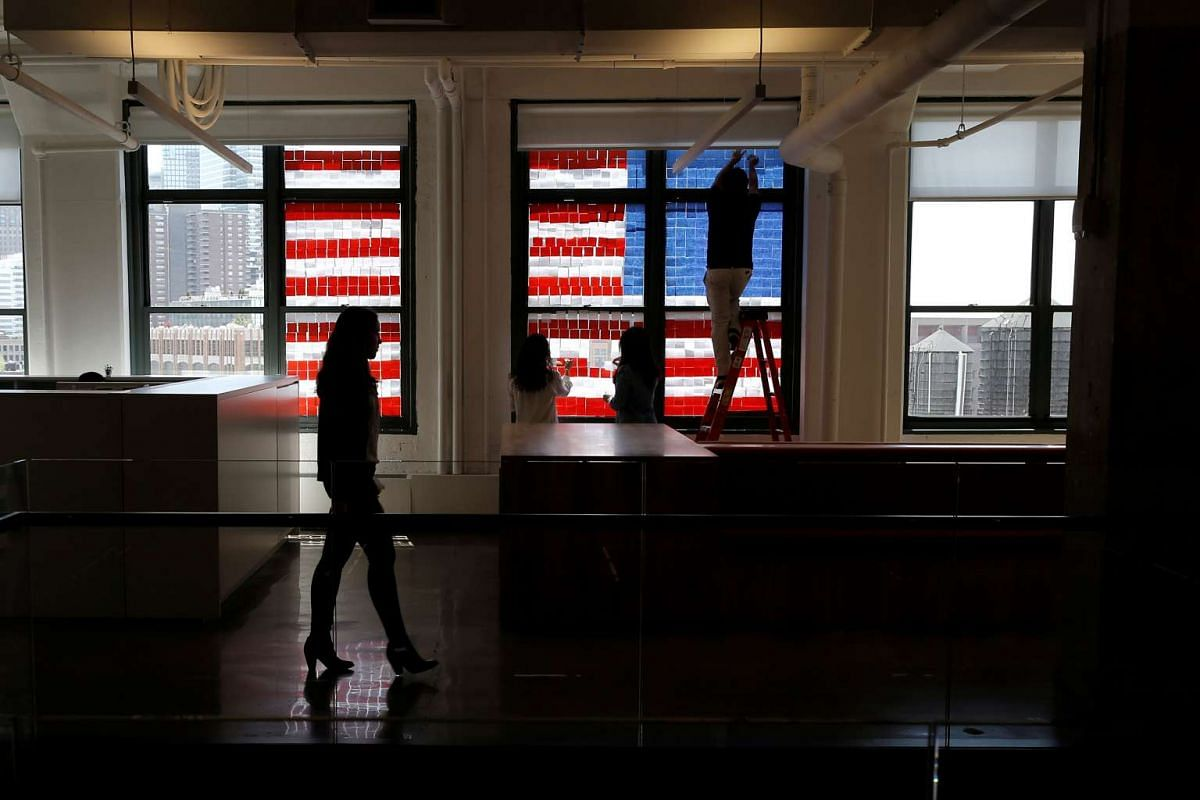 Employees create a US flag image on a window with Post-it notes at the Horizon Media offices at 75 Varick Street in lower Manhattan, New York.