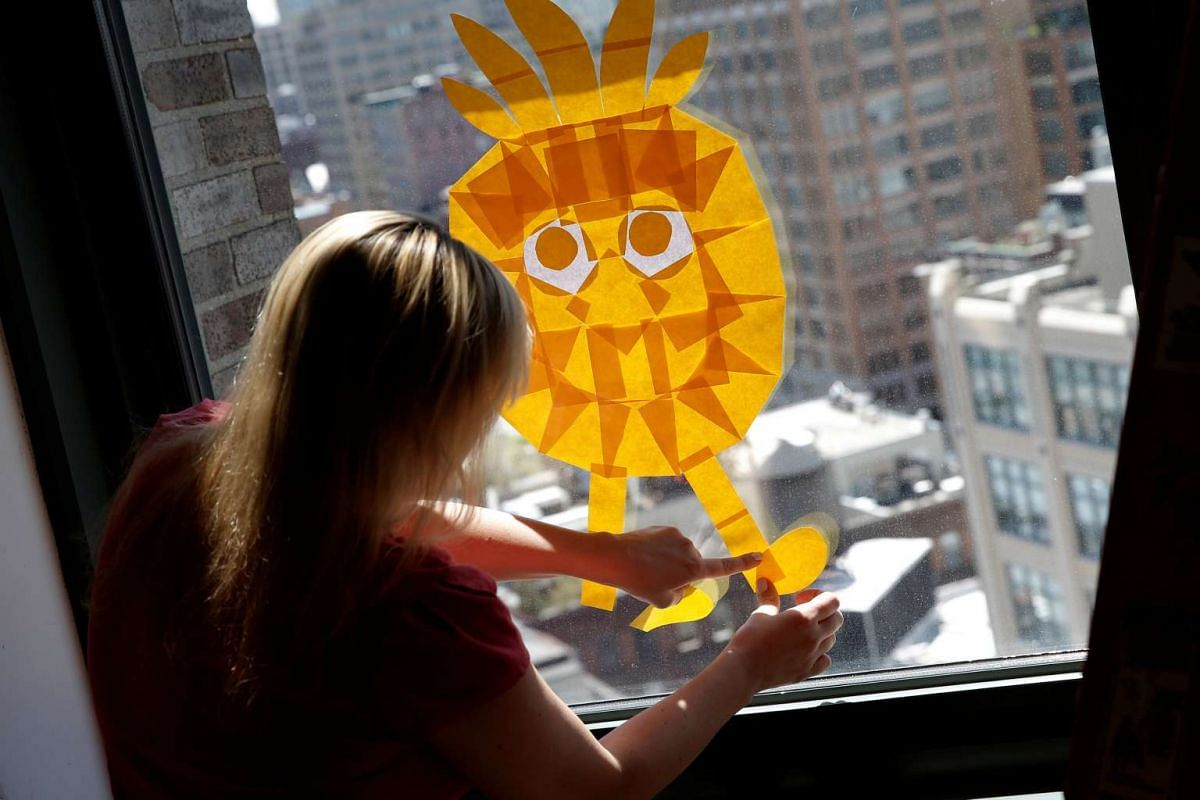 An employee creates an image on a window with Post-it notes at the Horizon Media offices at 75 Varick Street in lower Manhattan, New York.