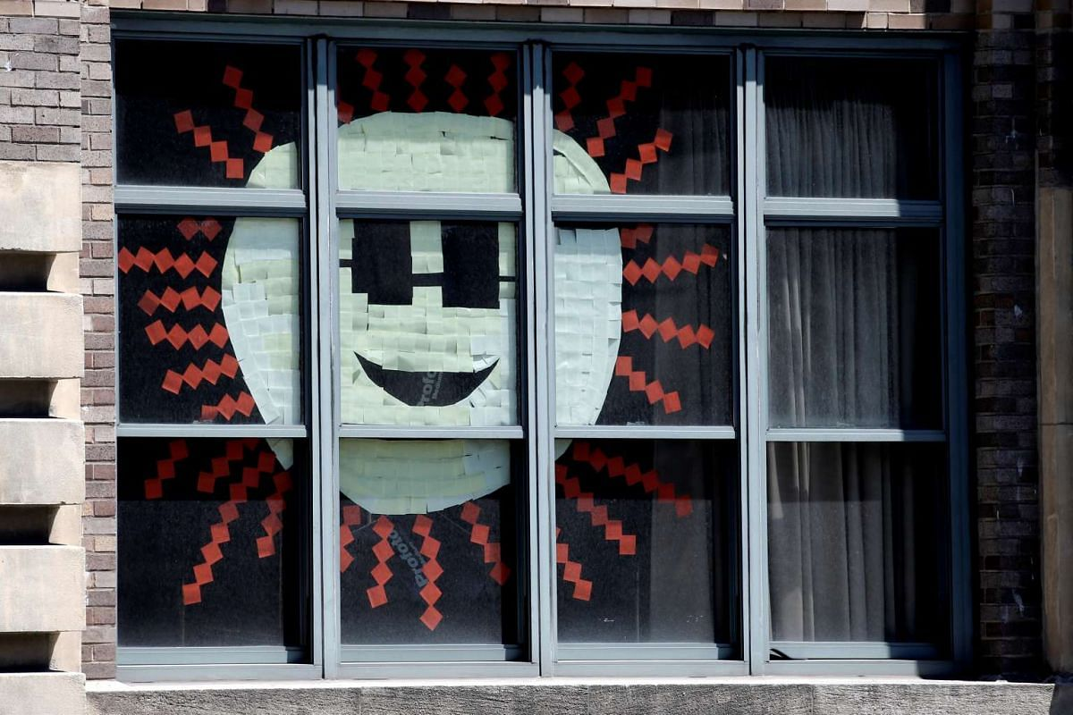 An image of the sun created with Post-it notes is seen in windows at 200 Hudson street in lower Manhattan, New York.