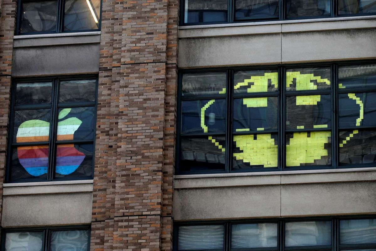 Images created with Post-it notes are seen in the windows of offices at 75 Varick Street in lower Manhattan, New York.