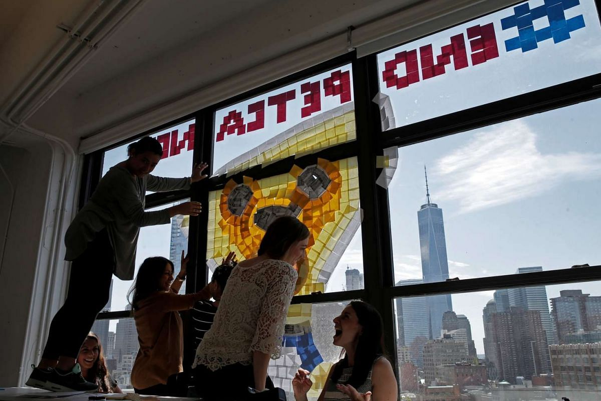 Employees create an image promoting pet cancer awareness month on a window with Post-it notes at the Horizon Media offices at 75 Varick Street in lower Manhattan, New York.
