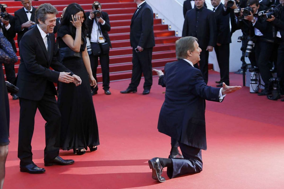 Director William Friedkin (right) posing as actor Willem Dafoe (left) and his wife Giada Colagrande (centre) look on as they arrive on the red carpet for the screening of the film Bacalaureat (Graduation) in competition at the 69th Cannes Film Festiv