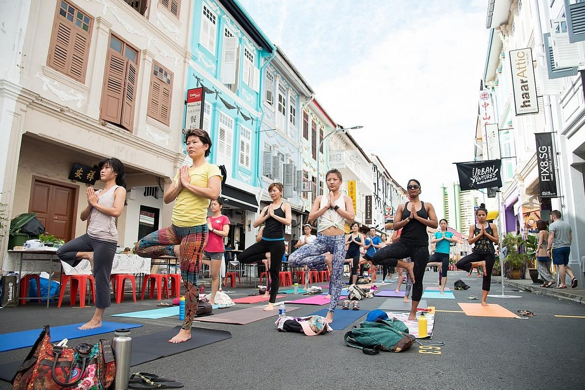 Haji Lane on a Sunday evening. People doing yoga in Keong Saik Road during Urban Ventures held there last month. Bussorah Street is closed to traffic on Friday night and the weekend.