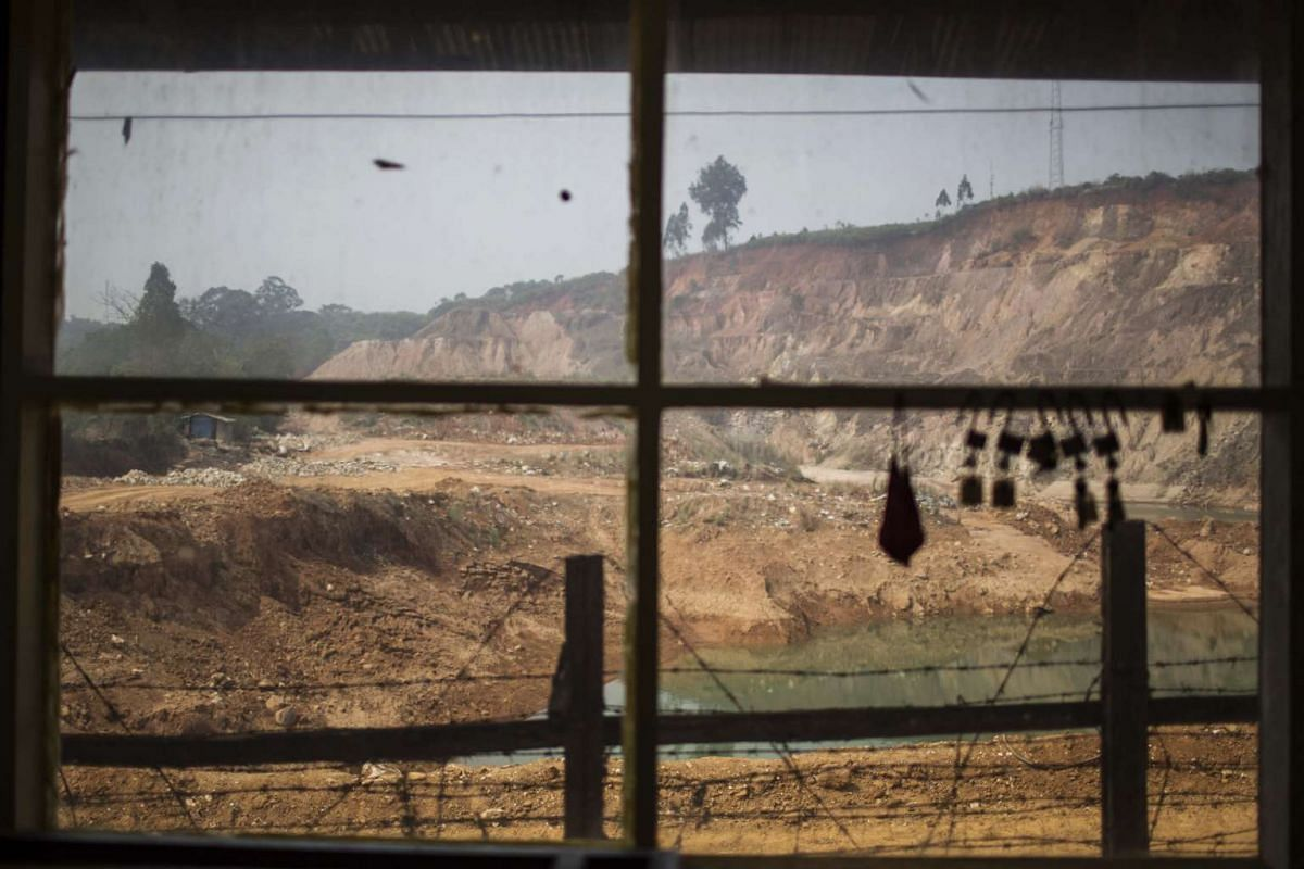 The Shwe Pyi Aye open pit mining site is seen through a window of a building in Mogok, Mandalay, Myanmar, on March 14, 2016.