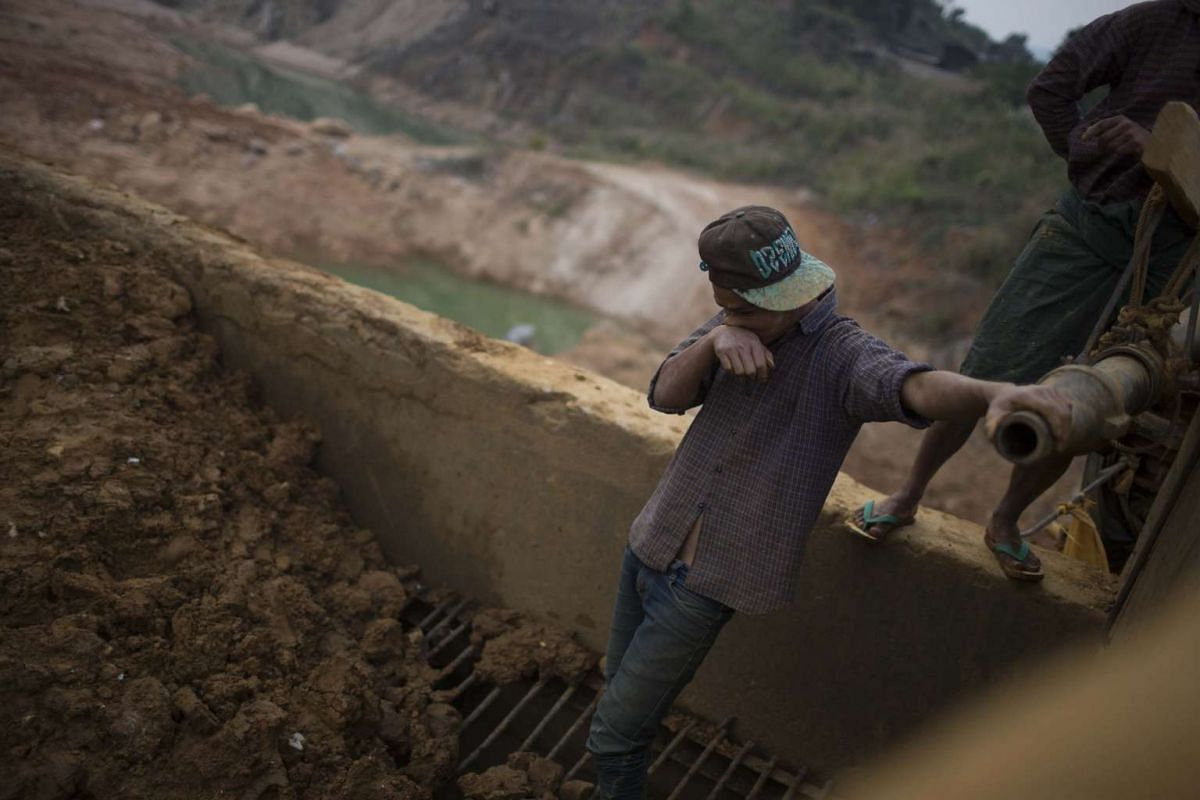 A miner searches for gemstones at the Shwe Pyi Ayeopen pit mining site in Mogok, Myanmar, on March 14, 2016.