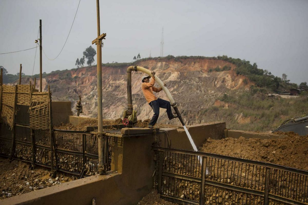 A miner operates a high powered hose to wash dirt off rocks at the Shwe Pyi Ayeopen pit mining site in Mogok, Myanmar, on March 14, 2016.