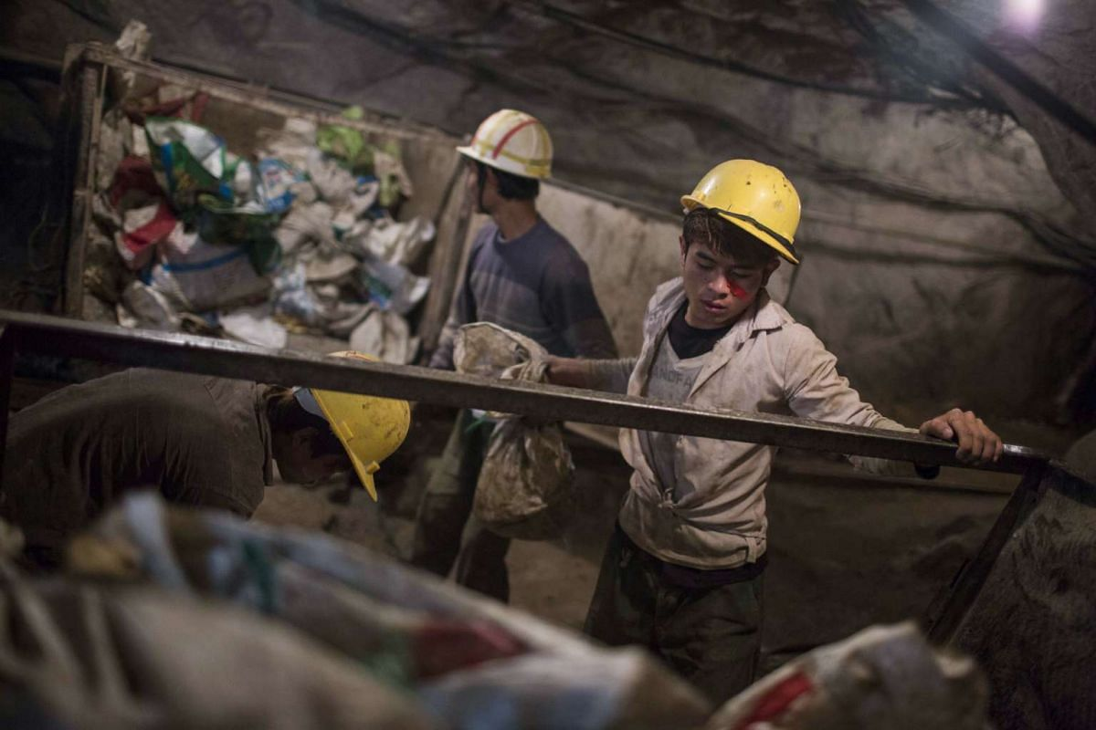 Miners load bags filled with rocks embedded with gemstones onto a cart at the Mogok Pride mine in Mogok, Myanmar, on March 14, 2016.