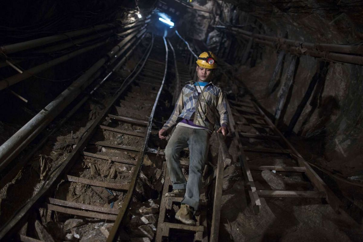 A miner descends a flight of steps into a mine shaft at the Mogok Pride mine in Mogok, Myanmar, on March 14, 2016.